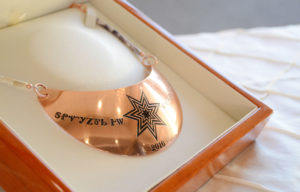 Honorees received a custom copper-plated gorget designed by Cherokee Nation metalsmith artist Toneh Chuleewah. The gorget featured the SevenStar emblem and their award name in Cherokee syllabary.